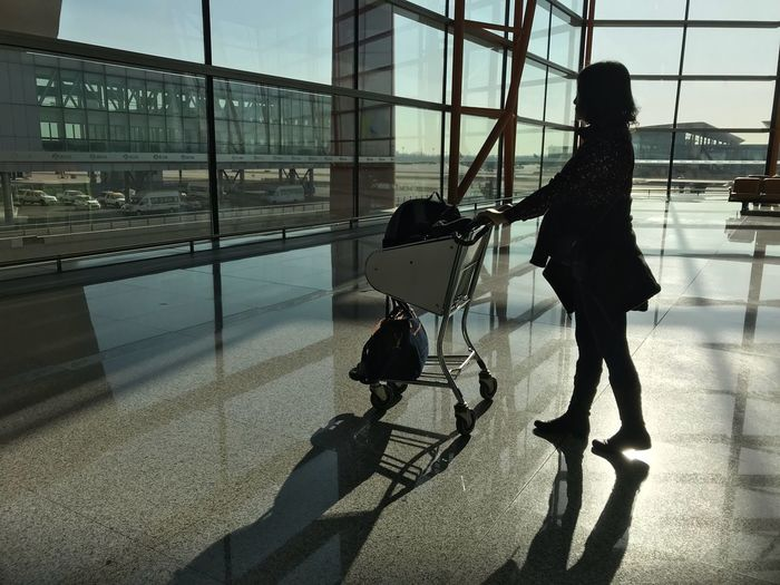 Woman holding luggage cart while in departure area