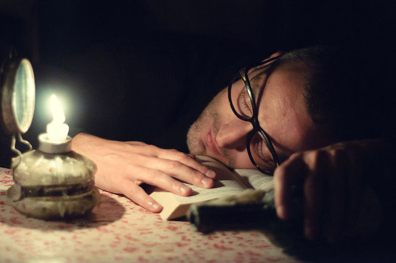 Book Sleeping Headshot Lighting Equipment One Person Eyeglasses  Portrait Technology Indoors  Illuminated Glasses Table Real People Young Adult Lifestyles Electric Lamp Concentration Adult Communication Lying On Front Light Teenager
