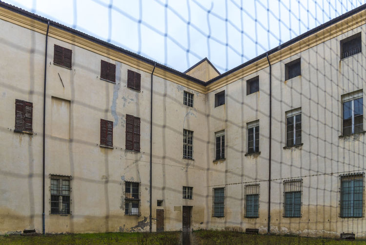 Abandoned prison shot behind rusted chain link fence Architecture Building Building Exterior Built Structure City Day Façade Glass - Material In A Row Low Angle View Modern Nature No People Outdoors Reflection Repetition Residential District Side By Side Sky Window