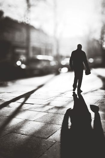 Tilt-shift image of silhouette man walking on sidewalk