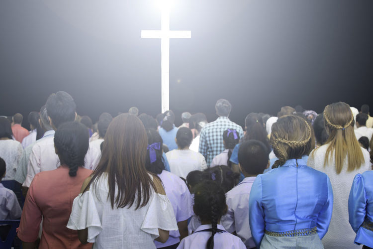 Crowd Standing In Front Of Illuminated Cross At Night