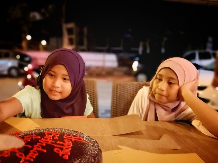 Sisters Sitting With Cake At Table During Night
