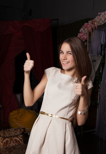 Portrait of happy young woman showing thumbs up while standing against black background