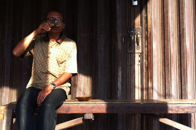 Old Man Sitting On Bench And Drinking Tea