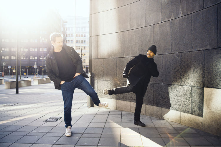 Men walking on sidewalk in city