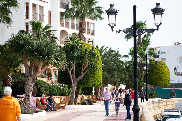 Ibiza Island, Spain - April 30, 2018: People walking by the seafront of Santa Eulalia. Santa Eulalia is a beautiful town and resort on the East coast of the Ibiza island Footpath Ibiza Island Mediterranean  Promenade SPAIN Santa Eulàlia Vacations Balearic Balearic Islands City Editorial  Group Of People Lush Foliage Outdoors Palm Tree Real People Seafront Sky Street Sunny Day Tourist Resort Town Travel Destinations Village Walkway