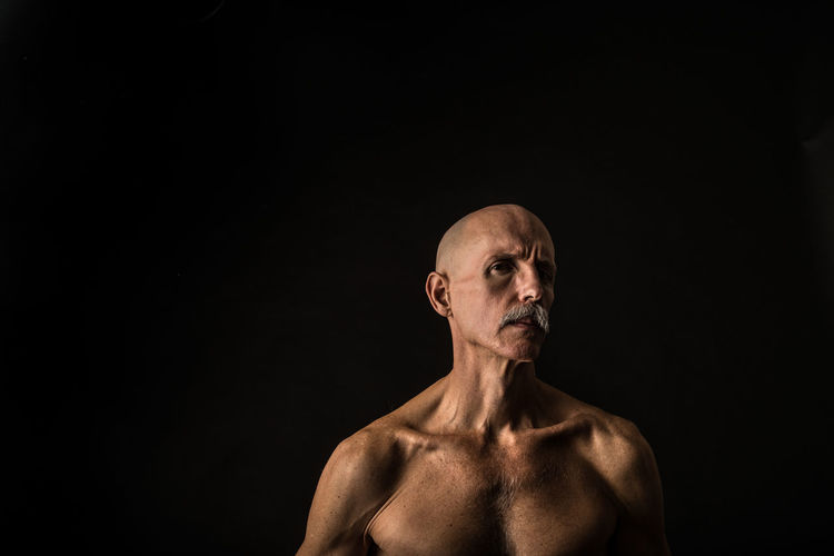 Portrait Of Shirtless Mature Man Against Black Background
