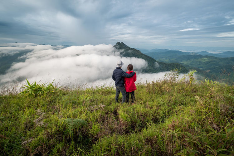 Happy couple feel freedom, enjoying the beautiful view in the mountains and looking together Portrait Love Travel Travel Destinations Outdoors Activity Grass Lifestyles Standing Tranquility Tranquil Scene Non-urban Scene Green Color Nature Sky Full Length Men Real People Mountain Plant Leisure Activity Scenics - Nature Rear View Beauty In Nature Cloud - Sky