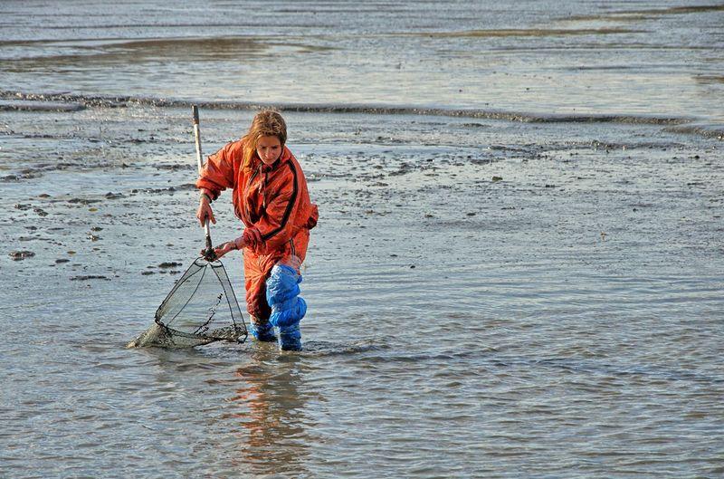 Boy fishing in muddy lake