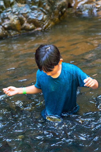 An asian boy feed and play with kelah fish in kelah sanctuary kenyir lake, terengganu.