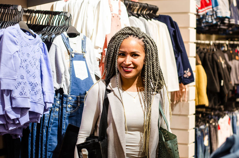 Portrait of smiling young woman standing in rack