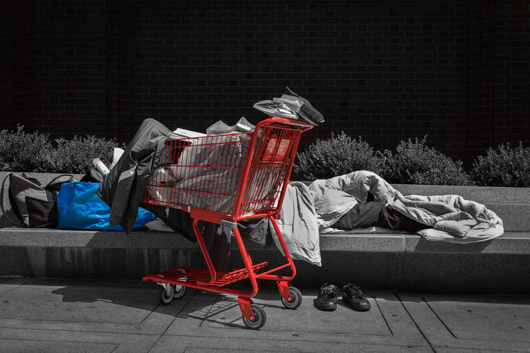 People sleeping on sidewalk against wall at night