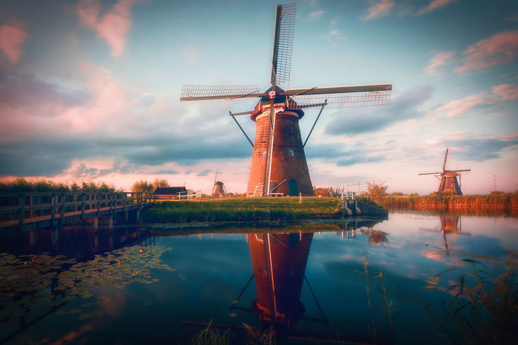 Traditional windmills by lake against cloudy sky