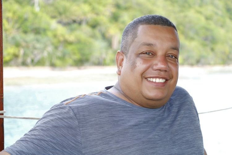 Close-up portrait of man smiling against sea