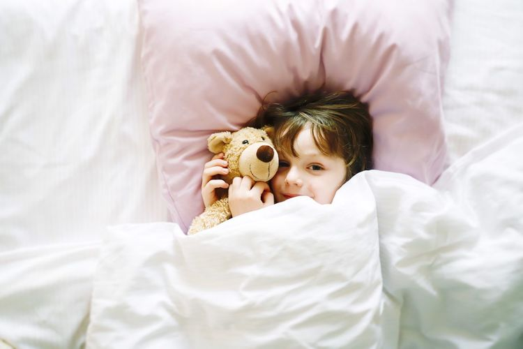 Directly above portrait of cute boy with teddy bear lying on bed at home