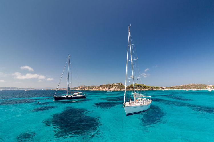 Sailboats sailing in sea against blue sky