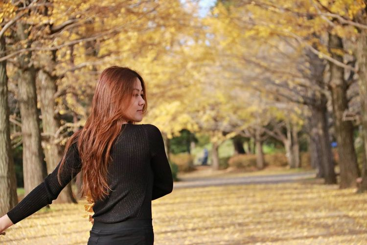 Young woman standing by tree during autumn