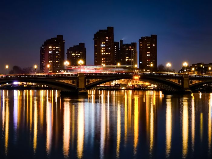 Battersea bridge and river reflections with silhouetted buildings in the background at night.