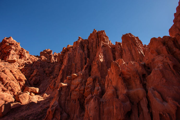Rock formations on mountain against blue sky