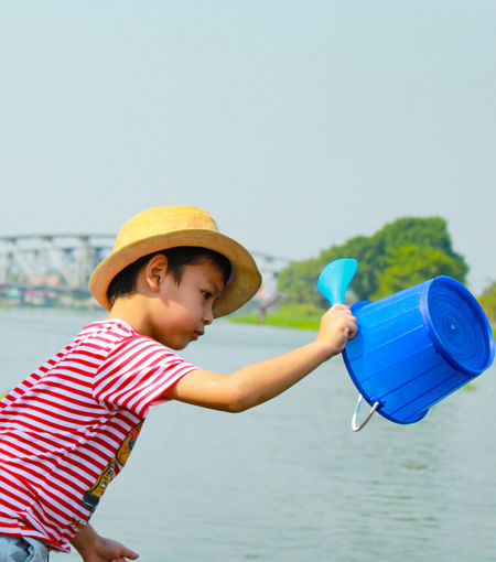 Children are feeding fish at the Tha Chin River Boys Child Childhood Copy Space Day Focus On Foreground Holding Innocence Leisure Activity Lifestyles Males  Men Nature One Person Outdoors Real People Side View Sky Water