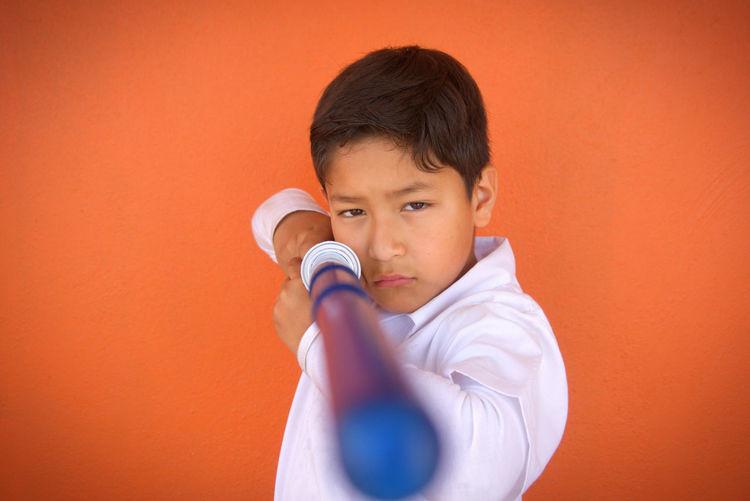 Portrait Of Boy Holding Toy Sword Against Orange Background