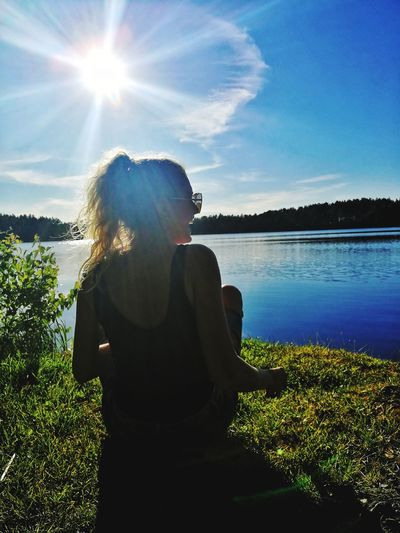 Rear view of woman sitting by lake against sky