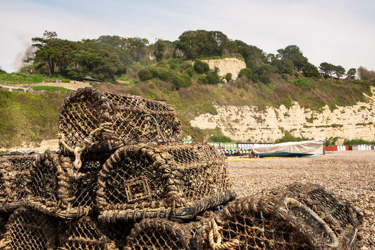 Empty crab pots piled up on a pebble beach with back drop of chalk cliffs, Beer, Devon, UK. Beer Devon Devon Coast South England Beer Chalk Cliffs Cliff Face Commercial Fishing Cove Crab Nests Crab Pots Devon Fishing Equipment Fishing Village Jurassic Coast Pebble Beach Seaside Village South Coast Tourist Attraction  Plant Nature Sky Tree Day No People Stack Land Hay Log Field Outdoors Water Tranquility Transportation Heap Mountain Landscape Animal Themes Architecture
