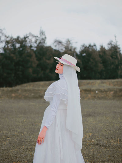 Side view of woman wearing hat standing outdoors