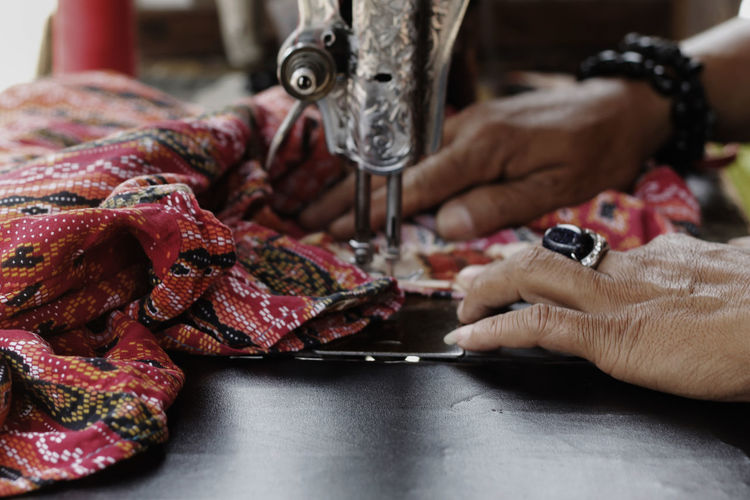 Cropped Hands Of Woman Sewing At Workshop