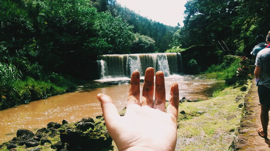 Close-up of person showing dirty hand by waterfall
