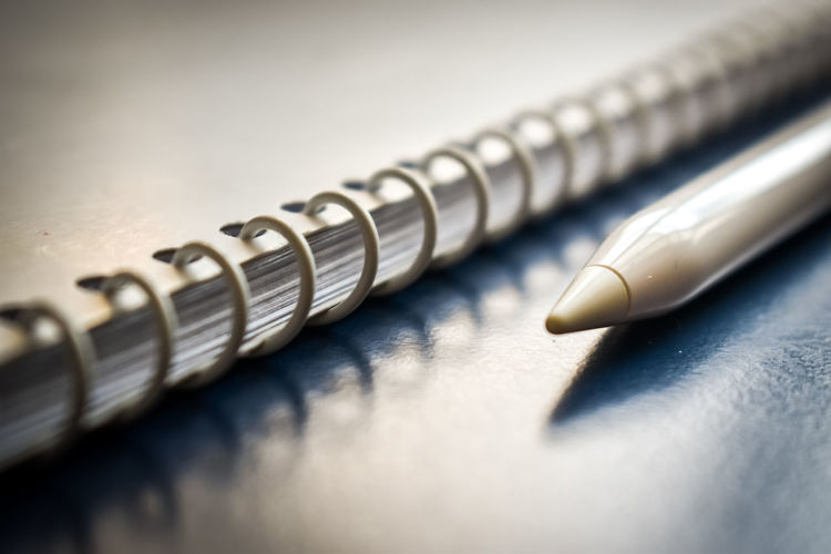 Close-up of digitized pen and spiral notebook on table