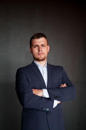 Portrait Of Well-Dressed Confident Businessman With Arms Crossed Standing Against Wall
