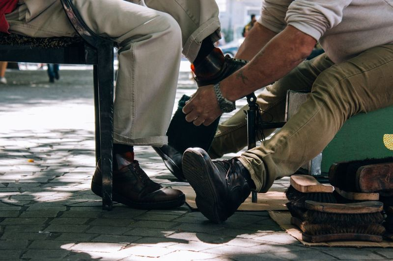 Low section of man polishing male customer shoe on footpath