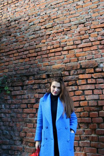 Portrait Young Women Looking At Camera Standing Front View Blue Brick Wall Jacket