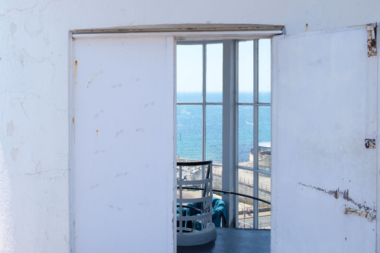 View of blue sea against sky seen through window