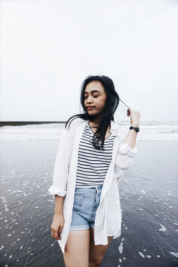 Beautiful young woman standing at beach against sky
