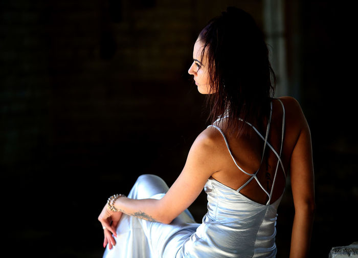 Rear view of mid adult woman in dress looking away while sitting outdoors at night