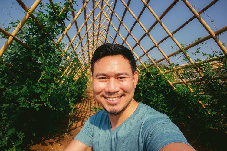 Portrait of smiling young man against plants
