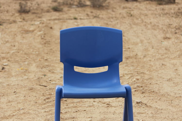 Close-up of empty chair on sand