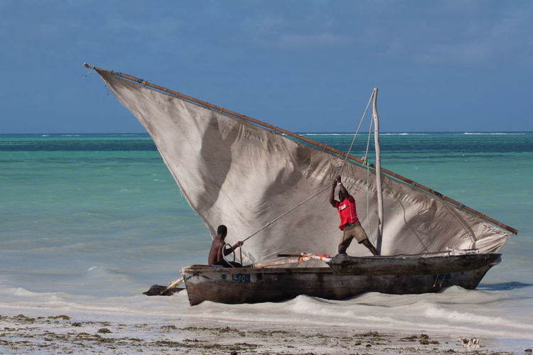 A dhow, the Tanzanian traditional sailboat. Africa Beach Blue Boat Cloud - Sky Fisherman Fishermen Horizon Horizon Over Water Outdoors Sail Sailboat Sand Sea Seashore Seaside Tanzania Traditional Transportation Travel Traveling Water Zanzibar Zanzibar_Tanzania