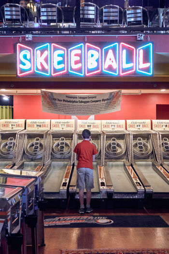 Rear View One Person Text Real People Illuminated Casual Clothing Full Length Communication Western Script Lifestyles Standing Leisure Activity Arts Culture And Entertainment Indoors  Machinery Architecture Adult Choice Technology Skeeball Game Arcade