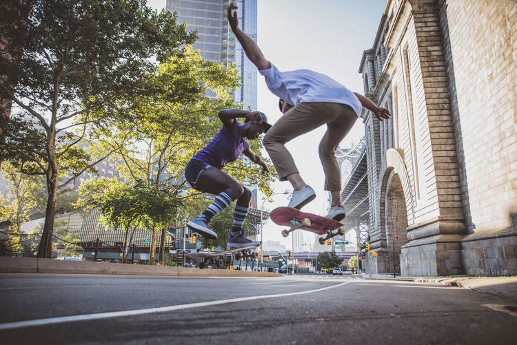 Young people jumping on skateboard in city