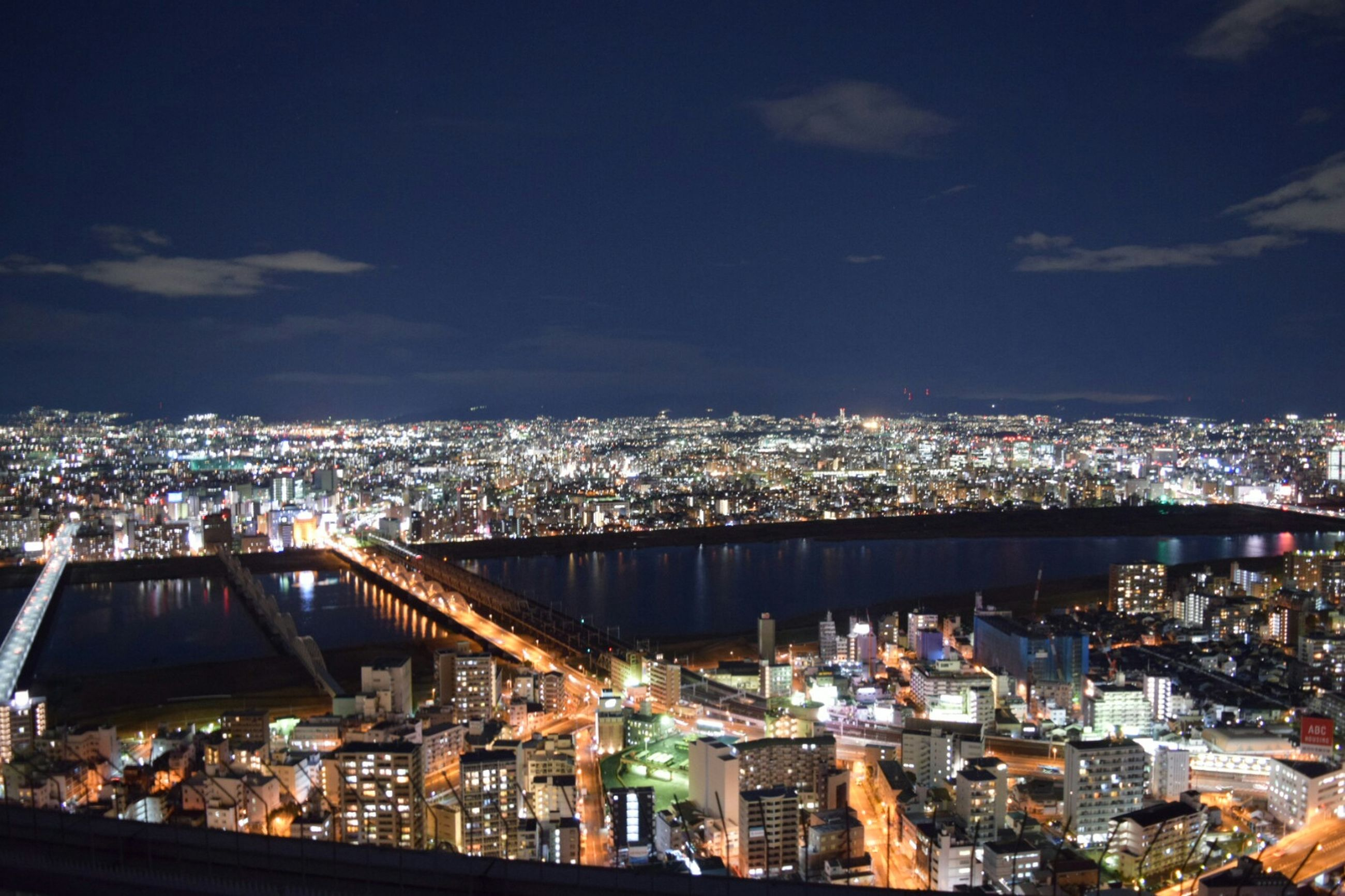 cityscape, city, architecture, illuminated, built structure, building exterior, crowded, night, sky, high angle view, residential district, modern, city life, skyscraper, river, capital cities, aerial view, residential building, travel destinations, water