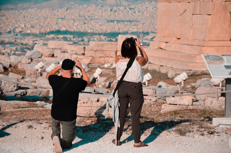 Rear view of couple photographing