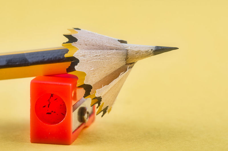 pencil with it shavings and sharpener over yellow background Close-up No People Still Life Yellow Studio Shot Indoors  Colored Background Art And Craft Pencil Craft Orange Color Creativity Focus On Foreground Wall - Building Feature Representation Wood - Material Writing Instrument Red Yellow Background Group Of Objects