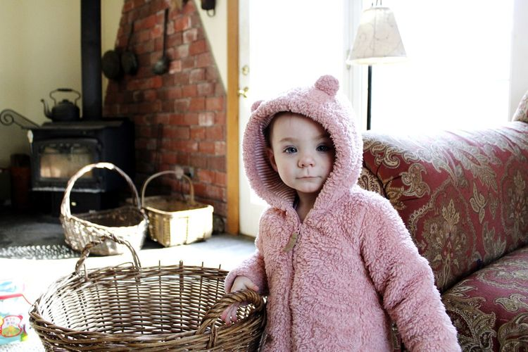 Portrait of cute baby girl by basket and sofa at home
