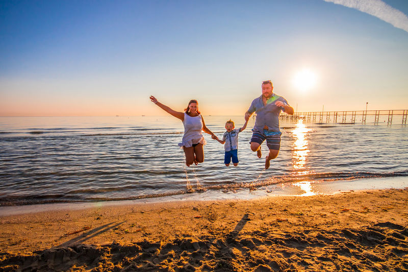 Parents Holding Son Hands While Jumping On Shore At Beach Against Sky During Sunset