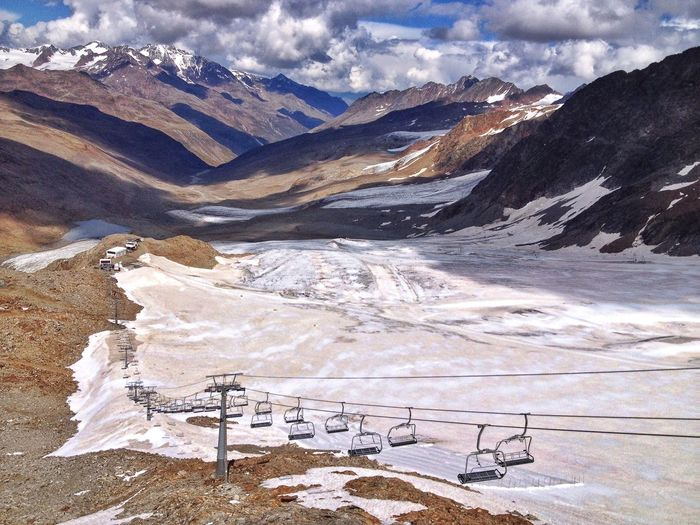 Scenic view of snowcapped mountains and overhead cable car against sky