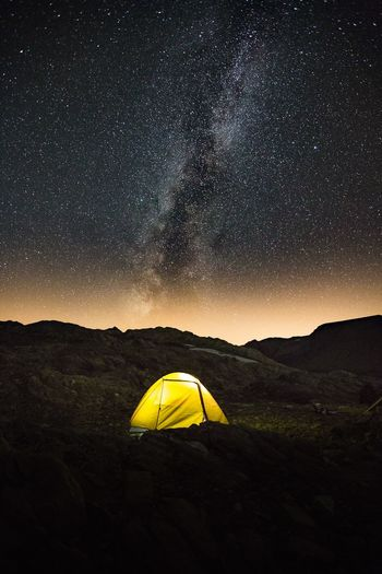 Yellow tent with a sky full of stars and the milky way