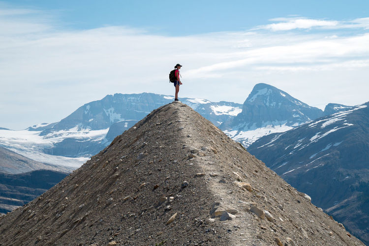 Low angle view of person standing on mountain against sky